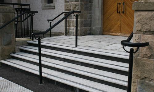 Гранитная лестница серого цвета на крыльце с противоскользящими чёрными вставками